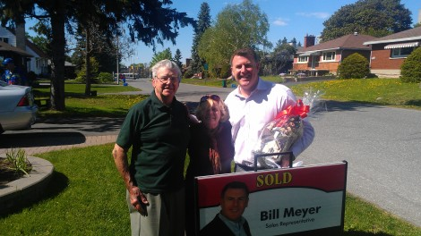 Bill Meyer and the old owners of 846 Iroquois stop to pose for a photo as they flip the sign to SOLD!