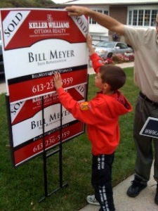 An eager helper flips Bill Meyer's sign to sold after Bill helped his parents sell their home in Glabar Park